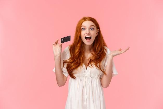 Unterhaltenes, verwundertes und aufgeregtes weibliches rothaarigemädchen des oberkörperporträts, das über große promos und prämien in der bank erzählt, kreditkarte hält und erstaunt, rosa wand lächelt