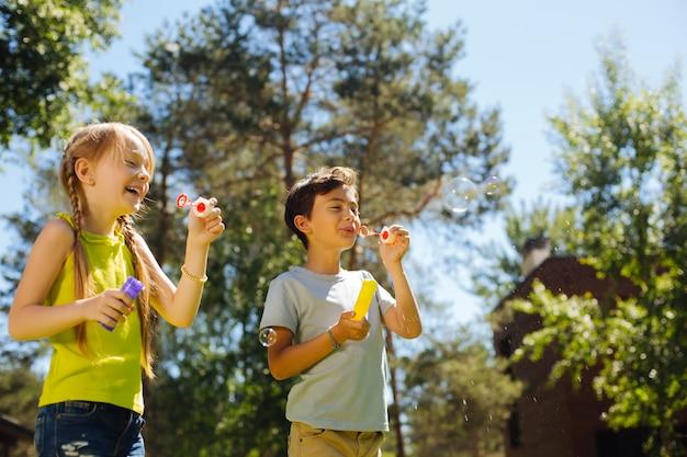 Unterhaltsam. glückliche entzückende kinder, die spaß haben und seifenblasen blasen