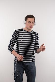Unterhaltsame unterhaltung. angenehmer junger mann, der kopfhörer trägt, während musik hört