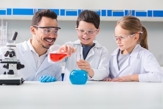 Unterhaltsame wissenschaft. positiver freudiger kluger junge, der eine flasche hält und flüssigkeit in eine andere flasche schmollt, während er ein experiment durchführt