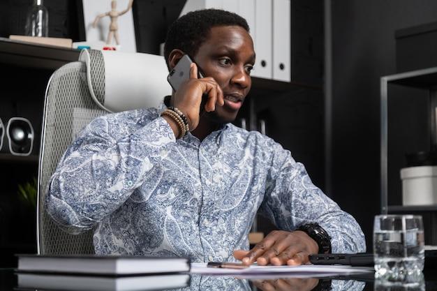 Unterhaltungshandy des jungen schwarzen geschäftsmannes, der am computertisch im büro sitzt