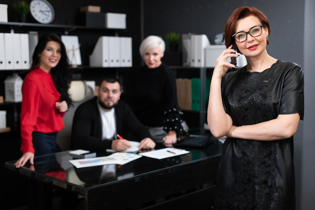 Unterhaltungstelefon der geschäftsfrau an von den büroangestellten, die projekt besprechen