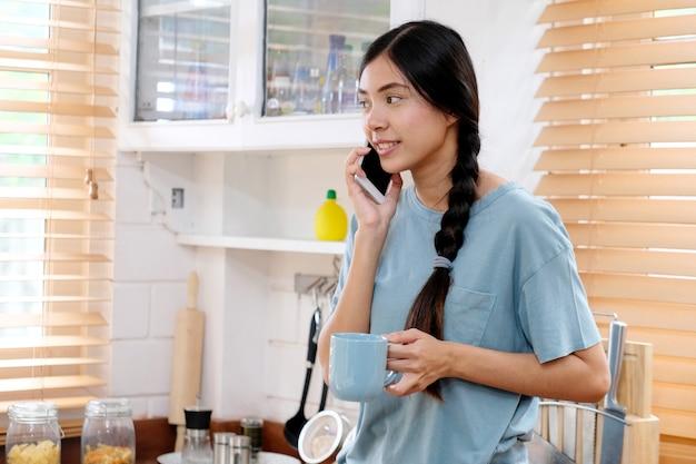 Unterhaltungstelefon der jungen jugendlichen asiatischen frau in der küche, asiatisches mädchen, das kaffeetasse bei der unterhaltung des intelligenten telefons mit lebensstil des glückes morgens, der leute und der technologie hält