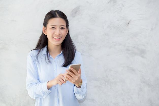 Unterhaltungstelefon und -lächeln der schönen asiatischen frau, die auf zementhintergrund steht ,.