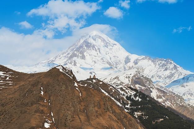 Unterkunft in einem bergdorf mit unglaublicher aussicht auf den berg kazbek. der blick aus dem fenster auf die schneebedeckte bergspitze, ein teil des daches des hauses im rahmen.