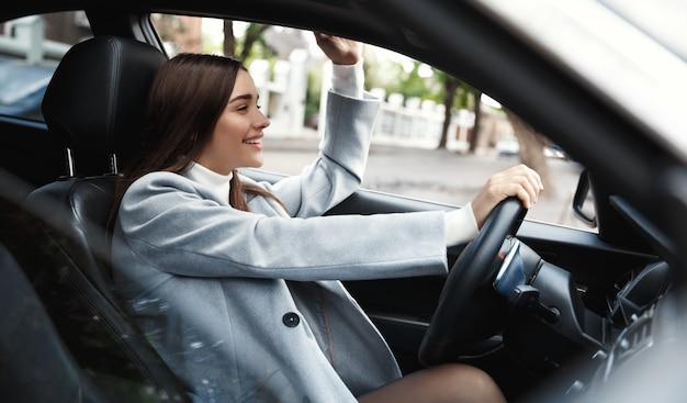 Unternehmen. glückliche geschäftige frau, die auto fährt und hand an freund winkt