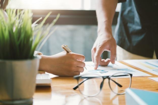 Unternehmensberater beschreibt einen marketingplan zur festlegung von geschäftsstrategien für unternehmerinnen mithilfe eines taschenrechners. konzept für unternehmensplanung und unternehmensforschung.