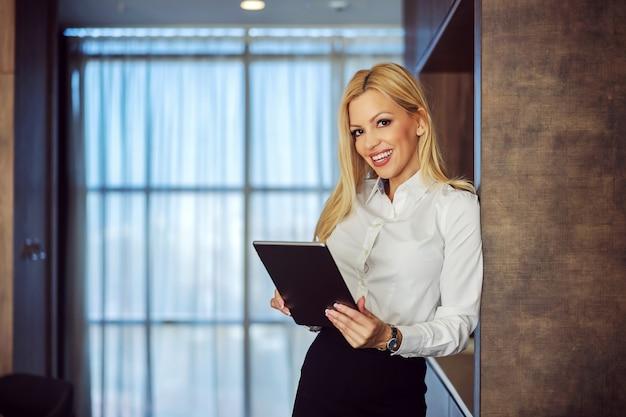 Unternehmensfotografie. hübsche blonde lächelnde frau, gut gekleidet mit dem arm an der wand, hält ein digitales tablet in den händen und lächelt in die kamera. sie trägt eine moderne uhr um ihr handgelenk