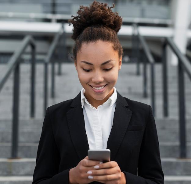 Unternehmensfrau, die telefon betrachtet