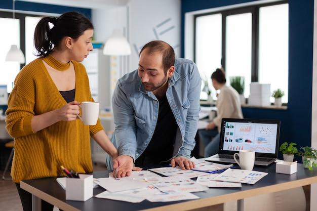 Unternehmensführung beim briefing gespräch mit blick auf marketingstatistik-charts