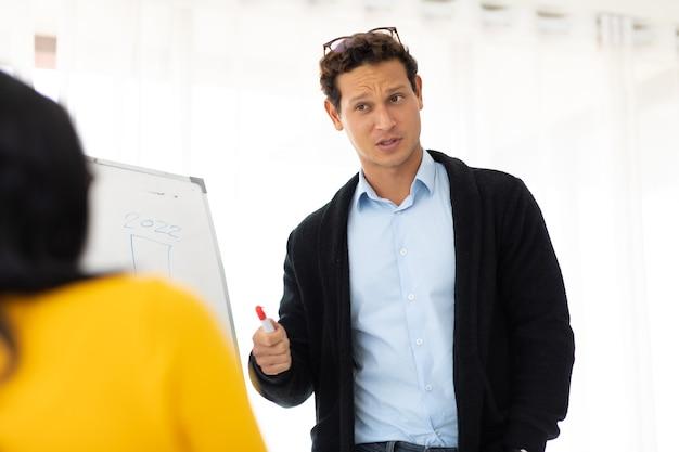 Unternehmensführungskonzept für unternehmen. hübscher hispanischer kreativer geschäftsmann, der beim treffen mit schwarzen freundinnen im arbeitsplatzbüro spricht.
