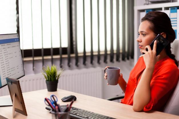 Unternehmensgeschäftsfrau am arbeitsplatz, die mit dem geschäftspartner in rot telefoniert. beschäftigter freiberufler, der mit dem smartphone vom büro aus arbeitet, um mit kunden zu sprechen, die am schreibtisch sitzen und das dokument betrachten.