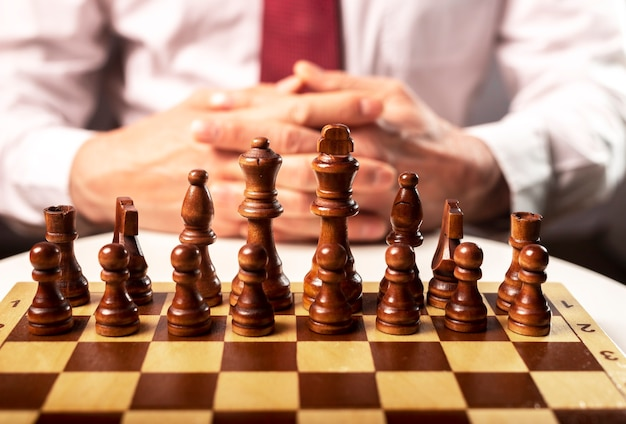 Unternehmensgründungs- und kontrollkonzept. männliche hände und schachbrett unter kontrolle des chefs.