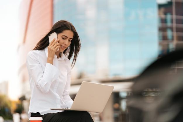 Unternehmenskommunikation. kaukasische geschäftsfrau, die am handy spricht, das draußen am laptop arbeitet, auf glasgebäude