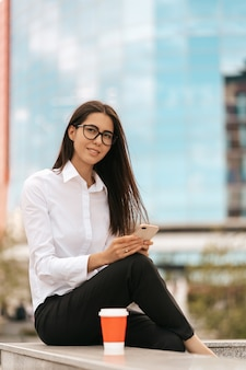Unternehmenskommunikation. kaukasische geschäftsfrau, die auf dem handy mit kaffee spricht, um auf glas zu gehen