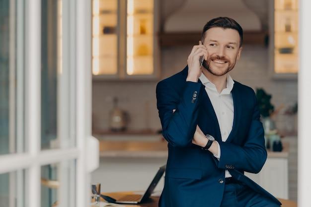 Unternehmenskommunikation. lächelnder professioneller bärtiger männlicher unternehmer hat erfolgreiche geschäftsgespräche und hält modernes smartphone in der nähe von ohrposen in der nähe des desktops, der in einem formellen anzug gekleidet ist.