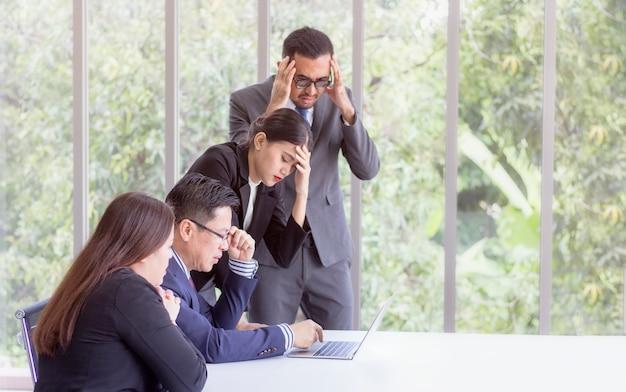 Unternehmenskonzept; betonter chef und führungsteam, die problemlösung bei der sitzung sucht, partner, die köpfe in den händen niedergedrückt durch schlechte nachrichten des ausfalls halten und über unternehmensproblem hoffnungslos sich fühlen