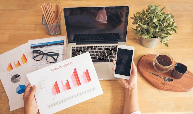 Unternehmenskonzept. junge schöne frau mit laptop und lesedokument bericht an ihrem tisch.