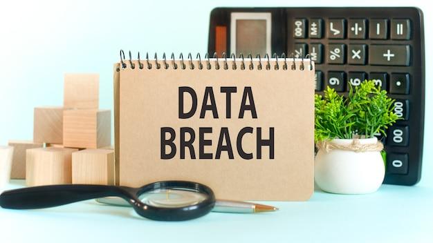 Unternehmenskonzept. notizbuch mit text data breach blatt weißes papier für notizen, taschenrechner, holzblöcke, lupe, an der kartenwand