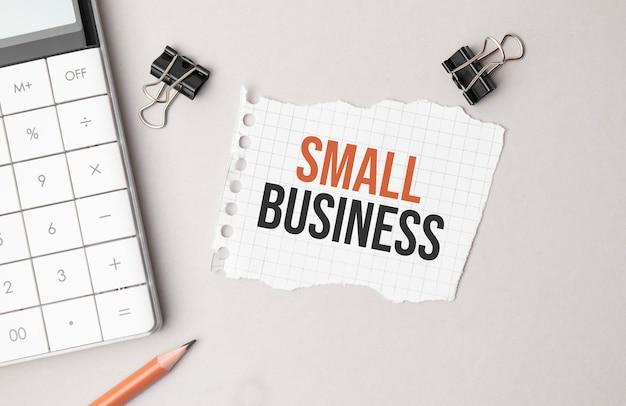 Unternehmenskonzept. notizbuch mit text small business blatt weißes papier für notizen, taschenrechner, brille, bleistift, kugelschreiber, im weißen hintergrund