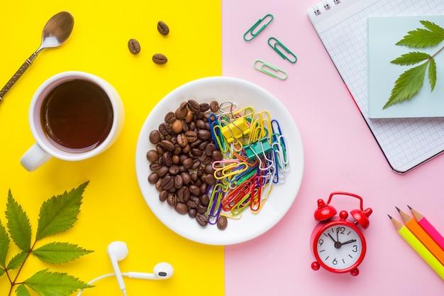 Unternehmenskonzept. notizbuch und briefpapier mit kaffeetasse und uhr auf gelbem und rosa mit pflanzenblättern.