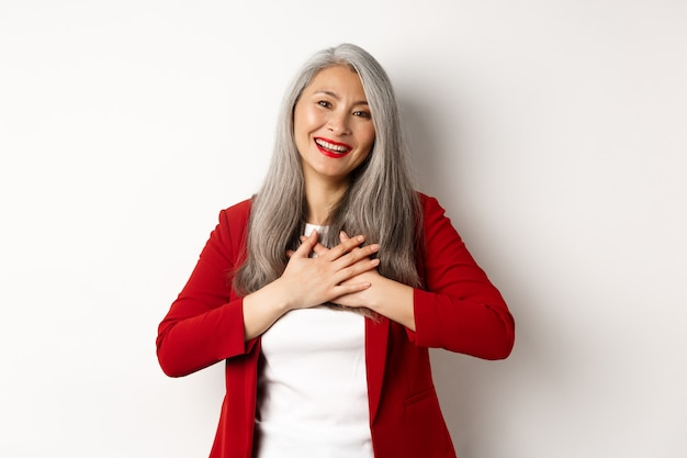 Unternehmenskonzept. reife asiatische frau mit roten lippen und blazer, händchen haltend am herzen und dankbar lächelnd, dankbar in die kamera schauend, über weißem hintergrund stehend.