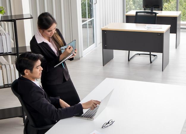 Unternehmensleiter, der den jungen persönlichen sekretärassistenten, teamleiter oder senior manager erklärt arbeitspflichten junior trainiert