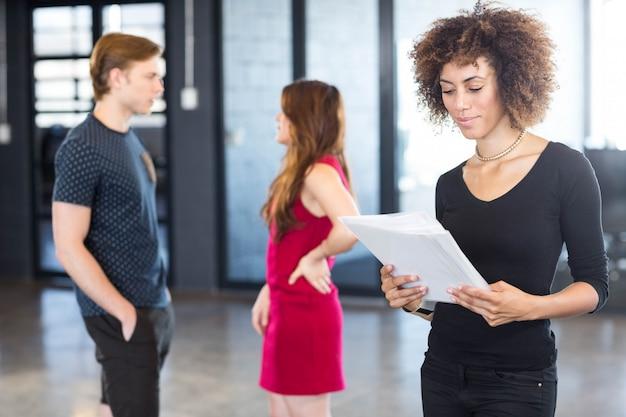 Unternehmensleiter, der ein auftragspapier im büro und in kollegen haben eine diskussion liest