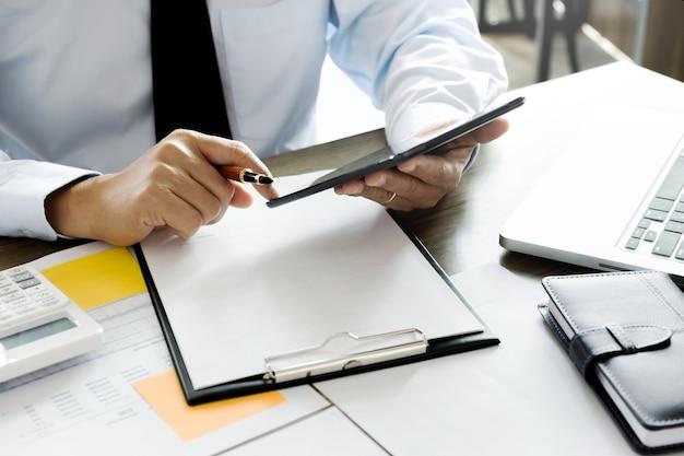 Unternehmensleiter, der tablette für datenreport-investition verwendet
