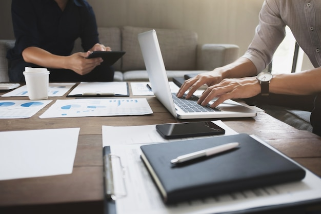 Unternehmensleiter, die auf bewertungsdatenpapier und digitaler ressource analysieren