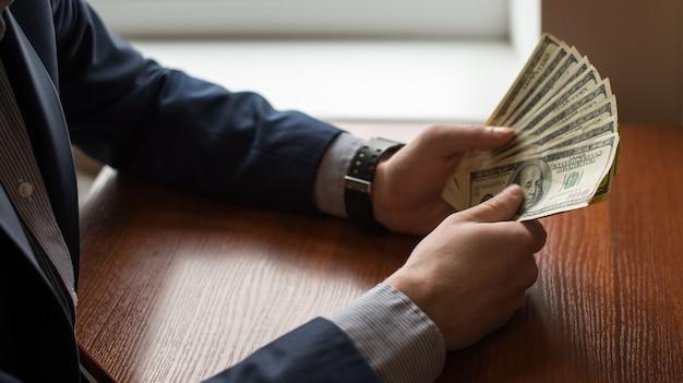 Unternehmensleiter im gesellschaftsanzug, der geld als bestechungsgeld gibt