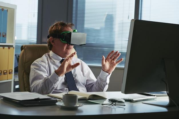 Unternehmensleiter in vr-kopfhörer in seinem büro