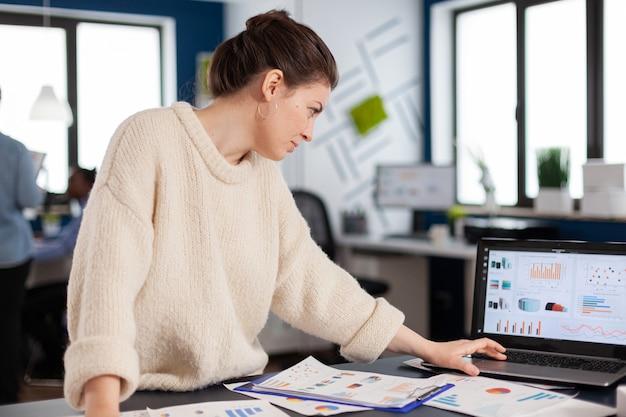 Unternehmensleiter liest, analysiert statistiken auf laptop im start-up-büro. executive entrepreneur, manager leader, der mit verschiedenen kollegen an projekten arbeitet. erfolgreicher unternehmensberuf