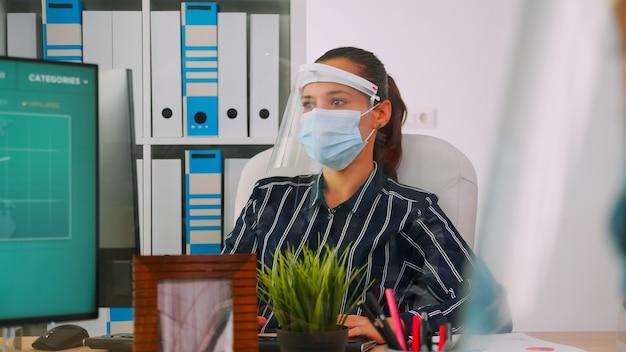 Unternehmensleiter mit gesichtsmaske, die auf dem computer tippt und während der coronavirus-pandemie in einem neuen normalen geschäftsbüro mit einem mitarbeiter diskutiert, der die soziale distanz respektiert. freiberufler mit moderner technologie