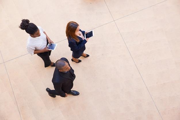 Unternehmensleiter und seine weiblichen assistenten, die durch büro gehen