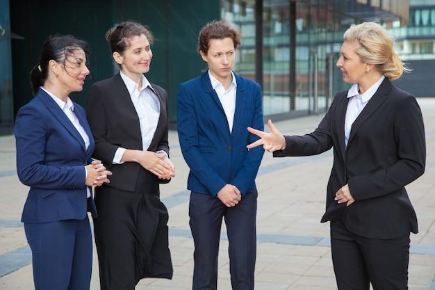 Unternehmensleiterin, die weibliches team unterrichtet und inspiriert. geschäftsfrauen, die anzüge tragen, treffen und sprechen in der stadt. führungs- und teamwork-konzept