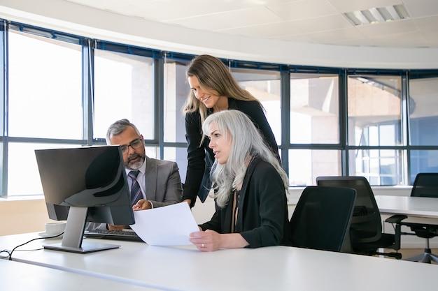 Unternehmensmanager diskutieren gewinn und analysieren bericht. geschäftsleute sitzen am besprechungstisch, beobachten am computermonitor und halten papier. geschäftskommunikations- oder teamwork-konzept