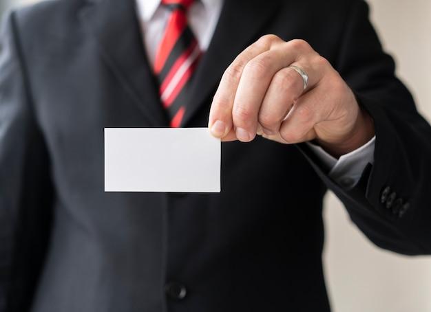 Unternehmensmann, der unbelegte visitenkarte anhält