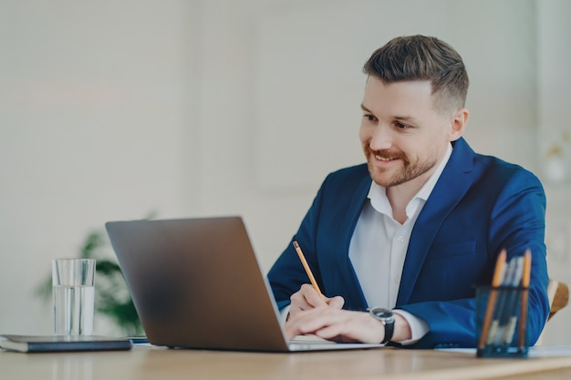 Unternehmensmitarbeiter in formellem anzug sitzt am desktop und konzentriert sich auf laptop-computer-posen im büroinneren schreibt informationen mit bleistiftuhren-tutorial-webinar durchsucht website macht forschung