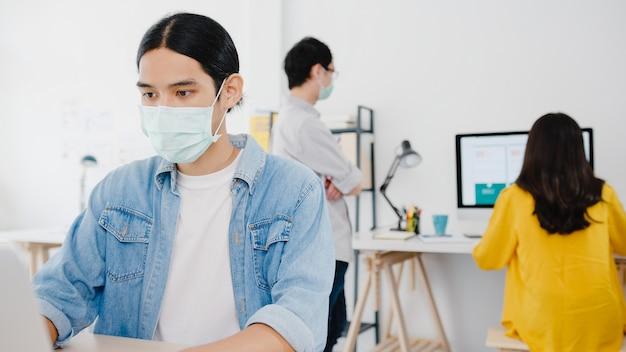 Unternehmer aus asien, der eine medizinische gesichtsmaske für soziale distanzierung in einer neuen normalen situation zur virenprävention trägt, während laptop wieder bei der arbeit im büro verwendet wird. lebensstil nach dem koronavirus.