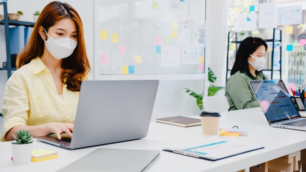 Unternehmer aus asien, die eine medizinische gesichtsmaske für soziale distanzierung in einer neuen normalen situation zur virenprävention tragen, während sie ihren laptop wieder bei der arbeit im büro verwenden. lebensstil nach dem koronavirus.