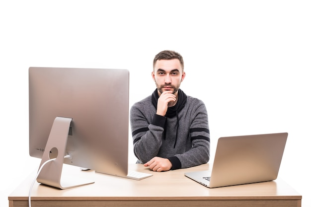 Unternehmer, der am tisch mit laptop und personalcomputer sitzt und kamera lokalisiert auf weiß betrachtet
