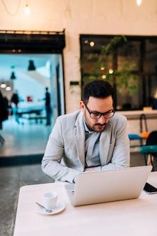 Unternehmer, der an einem laptop im café arbeitet.