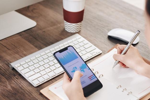 Unternehmer, der diagramm auf smartphonebildschirm analysiert