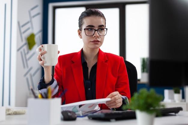 Unternehmer, der eine tasse kaffee im büro am arbeitsplatz hält