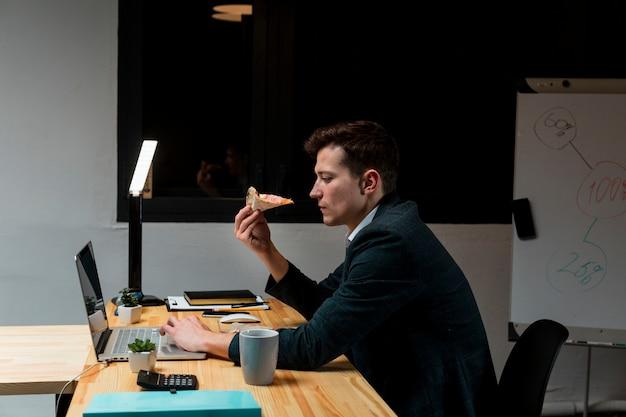 Unternehmer, der einen snack während der arbeit von zu hause aus hat