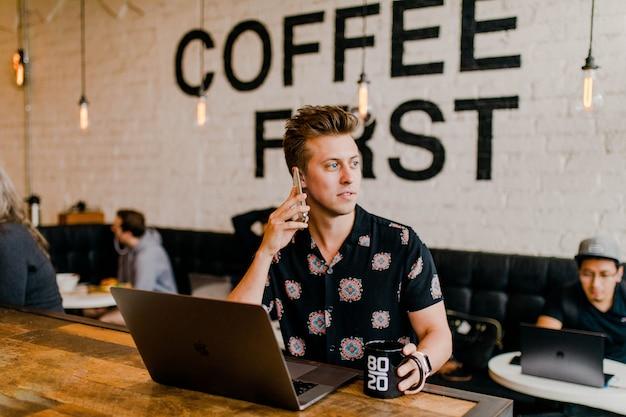 Unternehmer, der mit seinem laptop am café arbeitet