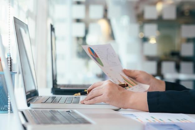 Unternehmer, der mobilen laptop für die analyse einer geschäftslösung verwendet.