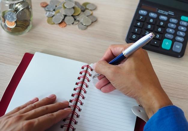 Unternehmer, der notizen macht und einen taschenrechner verwendet, um das haushaltseinkommen zu berechnen