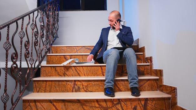 Unternehmer, die auf dem smartphone sprechen und jahresberichte auf der treppe des firmengebäudes überprüfen. überarbeiteter müder geschäftsmann, der während des telefonats mit dem unternehmensleiter die projektfrist liest.